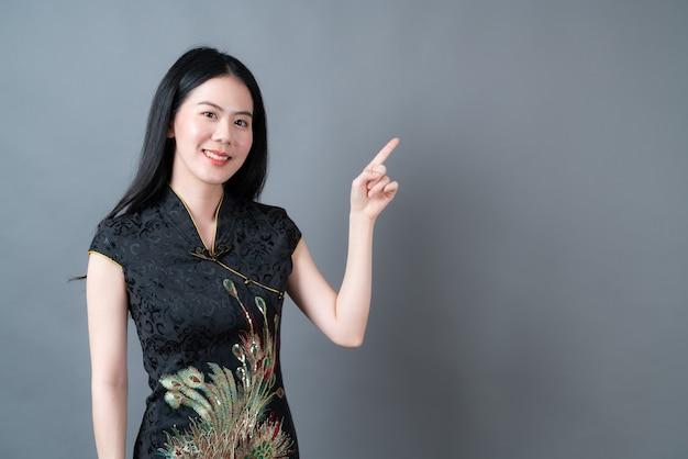 La bella giovane donna asiatica indossa il vestito tradizionale cinese nero con la mano che presenta sul lato nel muro grigio