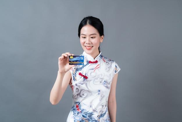 La bella giovane donna asiatica indossa il vestito tradizionale cinese con la carta di credito della tenuta della mano sul muro grigio