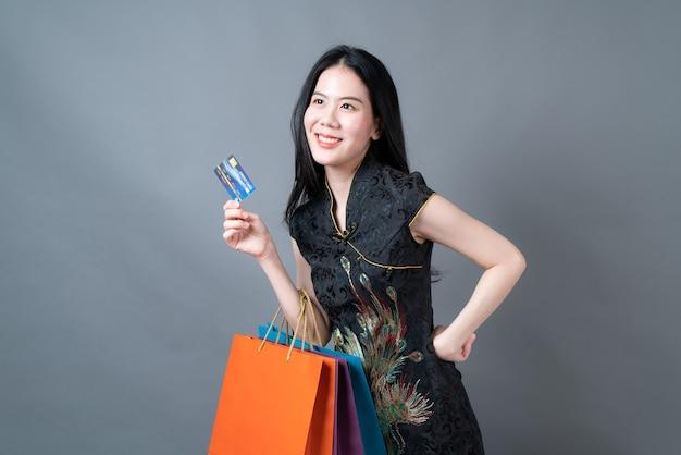 Bella giovane donna asiatica indossa abiti tradizionali cinesi con borsa della spesa e carta di credito sul muro grigio