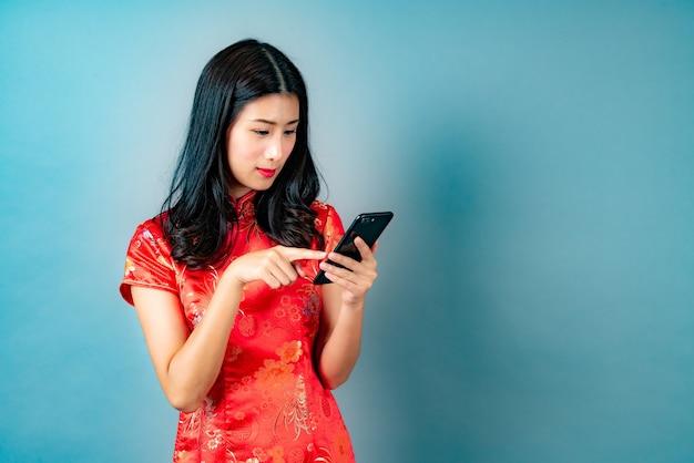 Bella giovane donna asiatica indossa un abito rosso cinese utilizzando lo smartphone con la faccia felice ed emozionata sul blu
