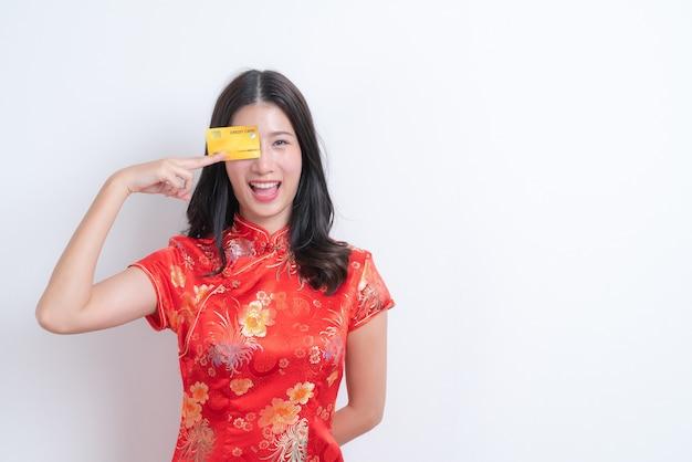 Bella giovane donna asiatica indossa un abito rosso tradizionale cinese tenendo la carta di credito per il capodanno cinese con muro bianco e copia spazio