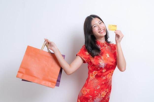 Bella giovane donna asiatica indossa un abito rosso tradizionale cinese tenendo la carta di credito e le borse della spesa per il capodanno cinese