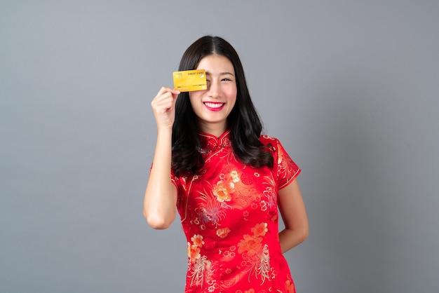 Bella giovane donna asiatica indossa un abito tradizionale cinese rosso con la mano che tiene la carta di credito per mostrare fiducia e sicurezza per effettuare il pagamento su sfondo grigio