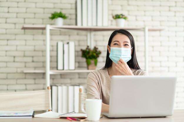 Bella giovane donna asiatica indossa una maschera chirurgica che lavora da casa e si sente felice sorridente con un'espressione gioiosa