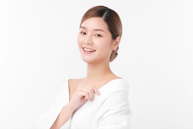 Bella giovane donna asiatica che indossa accappatoio su sfondo bianco, cura del viso, trattamento viso, cosmetologia, bellezza e concetto di spa.