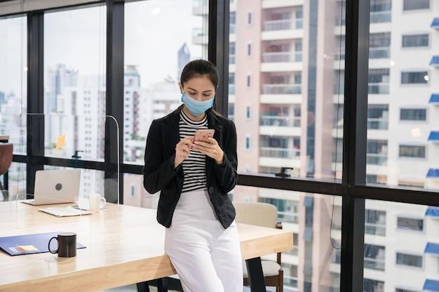 Bella giovane donna asiatica che indossa la maschera per il viso utilizza lo smartphone alla scrivania in legno nel nuovo ufficio normale.