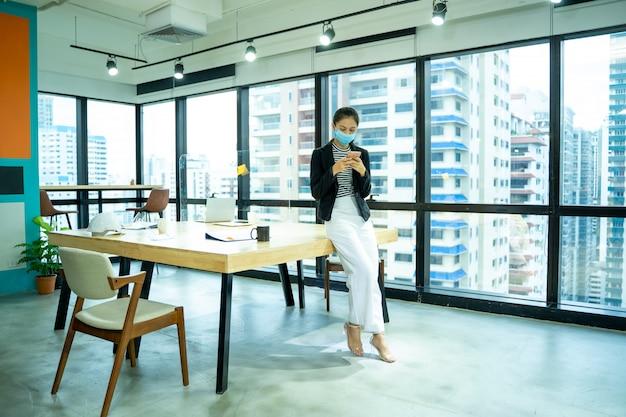 Bella giovane donna asiatica che indossa la maschera protettiva per proteggere contro il covid-19 che lavora in ufficio in un ufficio moderno.
