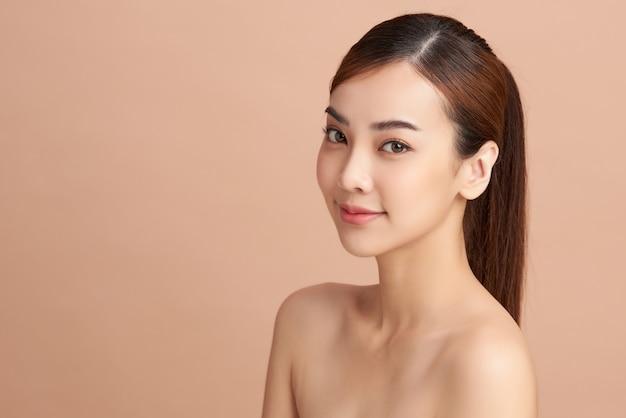 Bella giovane donna asiatica con pelle fresca e pulita su sfondo beige, cura del viso, trattamento viso, cosmetologia, bellezza e spa, ritratto di donne asiatiche.