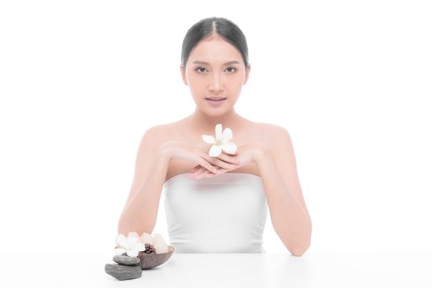 Bella giovane donna asiatica con pelle pulita, pelle fresca che tiene foglia tropicale fiore bianco in mano su sfondo bianco - colpo di bellezza di donna asiatica trattamento viso, cosmetologia, bellezza e spa c