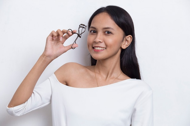 Bella giovane donna asiatica con piegaciglia isolato su sfondo bianco