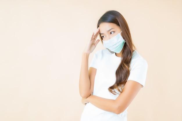 Bella giovane donna asiatica con maschera facciale pensando sul beige