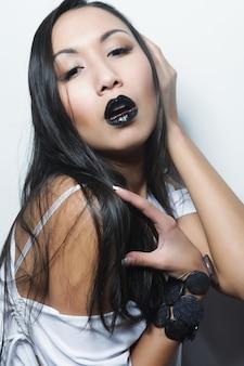 Bella giovane donna asiatica con pelle perfetta e rossetto nero, servizio di moda