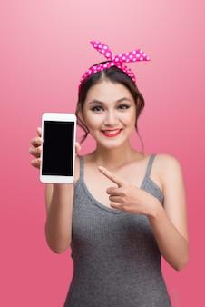 Bella giovane donna asiatica con trucco e acconciatura pin-up su sfondo rosa con telefono cellulare