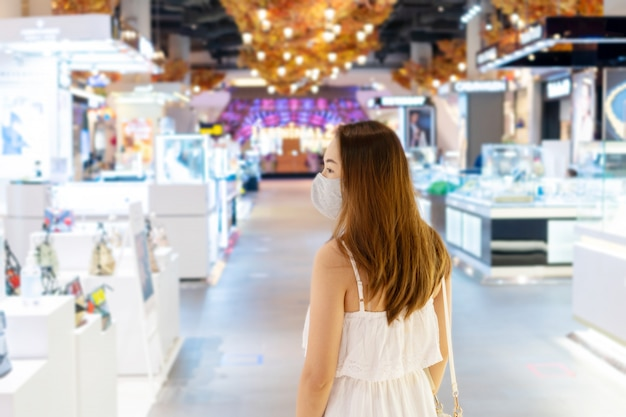 Bella giovane donna asiatica con la maschera di protezione ptotective che cammina al centro commerciale o al grande magazzino