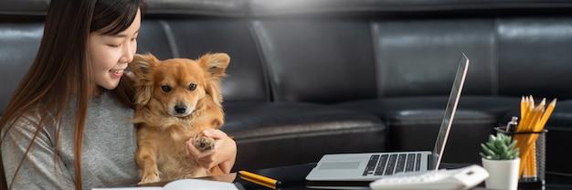 La bella giovane donna asiatica che lavora a distanza dalla casa e che sorride mentre si trova, ha buoni rapporti con con un animale domestico divertente del cane dell'assistente, concetto degli animali domestici del lavoro domestico.