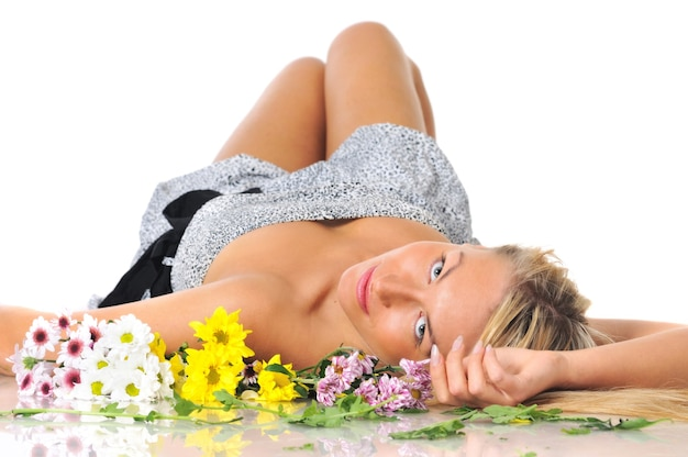Bella giovane donna bionda attraente si trova sulla schiena e guarda la telecamera su un bianco con fiori