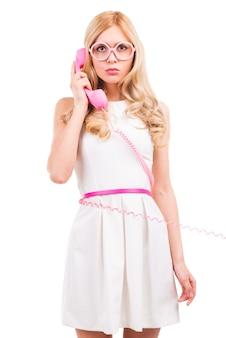 Bella giovane donna dei capelli biondi che parla sul telefono rosa e sorride