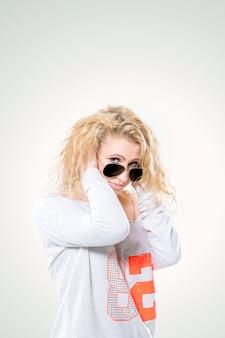 Bella giovane donna bionda con gli occhiali scuri e un maglione bianco su sfondo bianco