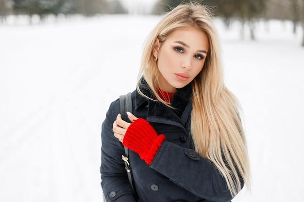 Bella giovane donna bionda in cappotto di moda con maglione rosso che cammina all'aperto su sfondo innevato