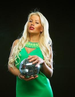 Bella giovane donna bionda che tiene la palla da discoteca al night club