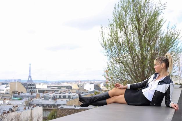Bellissima giovane donna bionda sdraiata sul tetto in gonna corta e stivali tacco alto a parigi