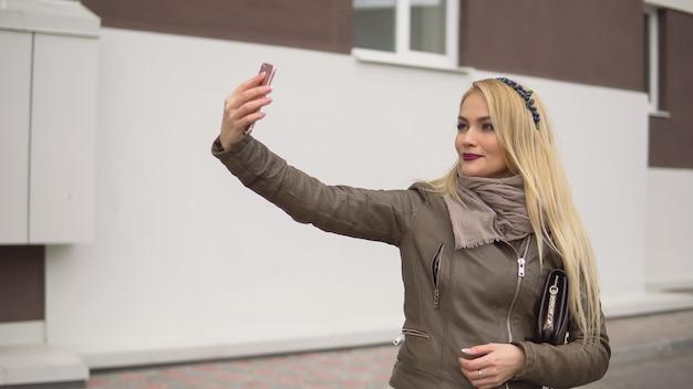Bella giovane donna bionda in sciarpa calda e giacca beige con borsa che fa selfie su smartphone in piedi sullo sfondo dell'edificio della città
