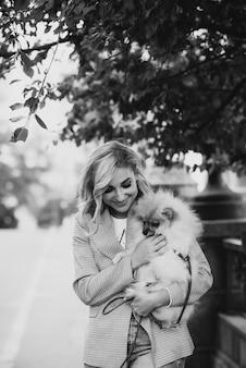 Bella giovane donna bionda con la sua razza di cane pomeranian per la passeggiata. cagnolino birichino. foto d'arte in bianco e nero.