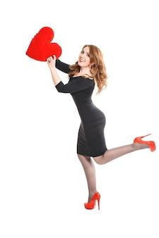 Bella giovane donna bionda con labbra rosse in abito nero e scarpe tacco alto con un cuore rosso nelle mani su uno sfondo bianco, san valentino, trucco di lusso alla moda