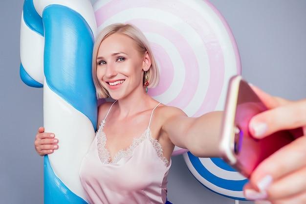Bella giovane bionda barbie dolce donna pasticcere modello sexy trucco perfetto abbraccia un enorme lecca-lecca con nastro di misurazione e scatta foto selfie su sfondo telefono caramelle finte dolci in studio shot