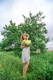 Una bella ragazza bionda ha raccolto un mazzo di fiori di campo. goditi una passeggiata in una calda giornata estiva.