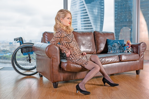 Una bella ragazza bionda in un vestito alla moda con una disabilità, in posa su un divano in pelle sullo sfondo di una sedia a rotelle.