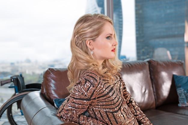 Una bella ragazza bionda in un vestito alla moda con una disabilità, in posa su un divano in pelle contro la superficie di una sedia a rotelle