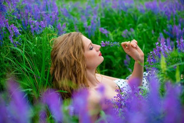 Bella giovane ragazza bionda in un campo verde tra fiori viola.
