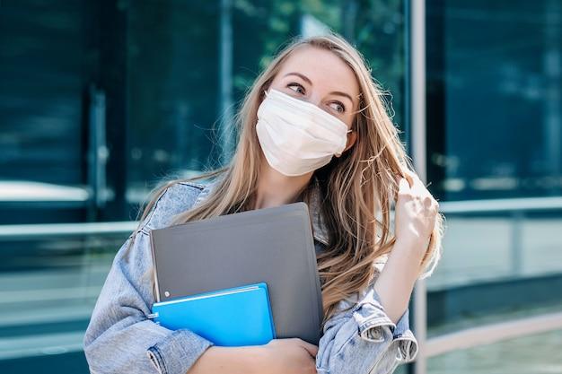 Bella giovane ragazza bionda in una maschera protettiva si trova sullo sfondo di un edificio moderno