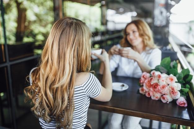 Capelli della bella giovane ragazza bionda dalla parte posteriore sulla caffetteria sulla terrazza estiva.
