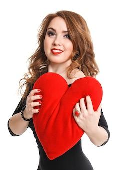 Una bella ragazza bionda con le labbra rosse su uno sfondo bianco isolamento in un vestito nero e un cuore rosso in mano, trucco di lusso elegante di moda, premuto al suo cuore.
