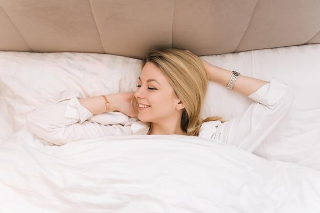 Bella giovane ragazza sorridente bionda sdraiata in un letto bianco, buongiorno allegra