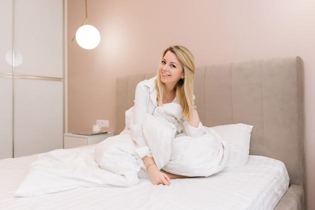 Bella giovane ragazza sorridente bionda che si siede in una coperta in un letto bianco, buongiorno allegra
