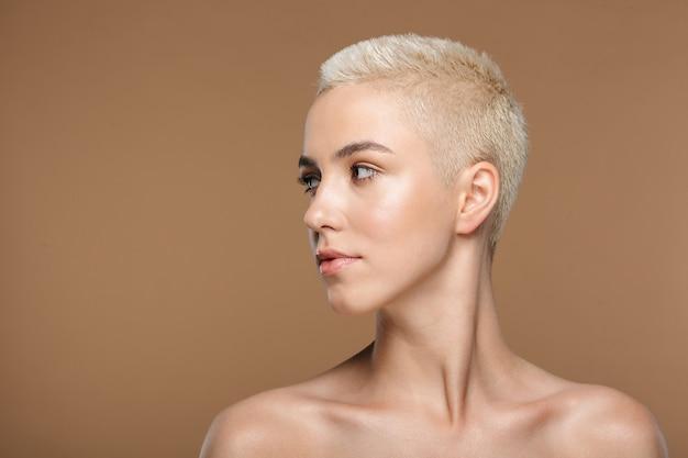 Una bella giovane donna bionda alla moda con taglio di capelli corto in posa isolata sopra la parete del muro beige scuro.