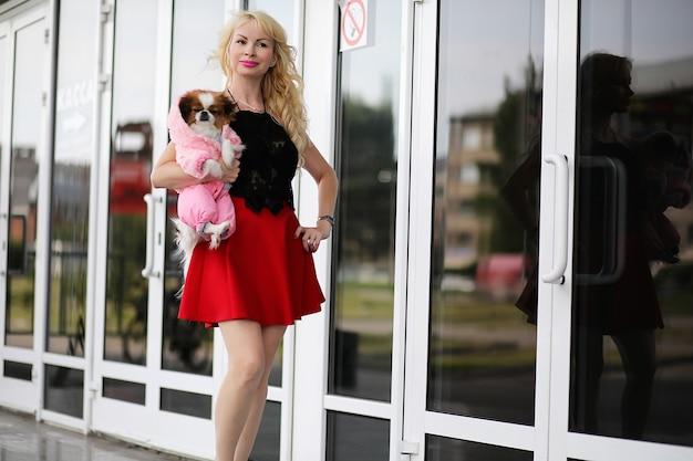 Bella giovane bionda a passeggio con il cagnolino