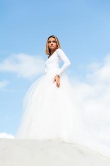 Bella giovane sposa bionda della donna in vestito bianco all'aperto