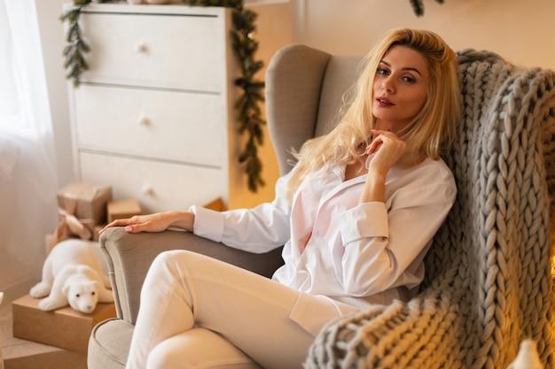 Il modello di bella giovane donna bionda in abiti bianchi alla moda con una camicia e jeans si siede su una sedia vicino a decorazioni natalizie e regali a casa. riposo e vacanze