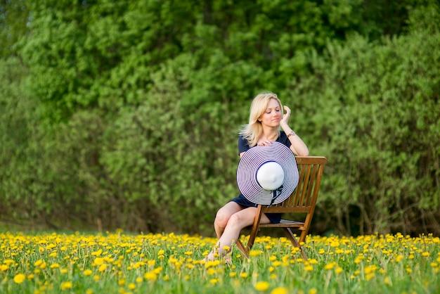 Una bella giovane donna bionda si rilassa in un prato fiorito di tarassaco durante l'estate