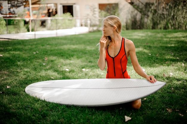 Bella e giovane donna bionda che si siede sul prato verde con un wakeboard