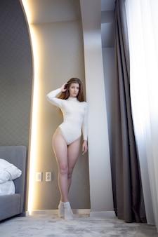 Una bella giovane donna bionda in biancheria intima si aggiusta i capelli in piedi vicino alla finestra