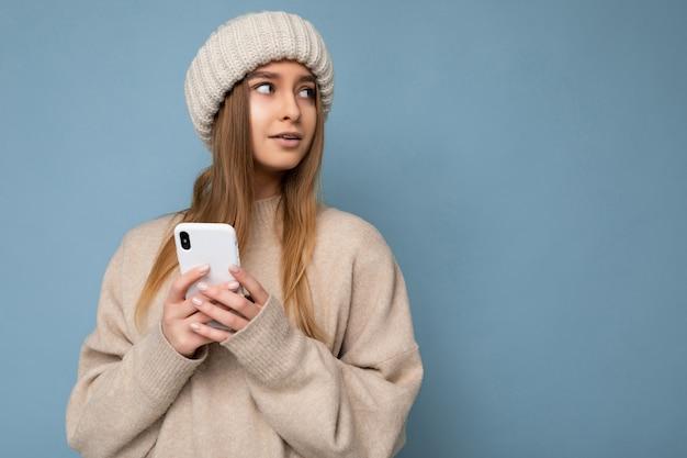 Bella giovane donna bionda che indossa un maglione caldo beige elegante e un caldo inverno lavorato a maglia