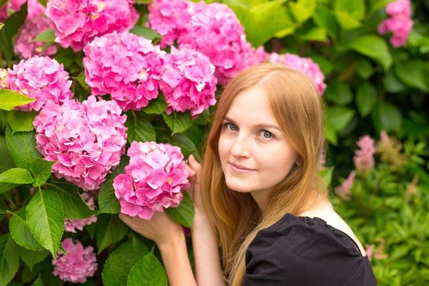 Bella giovane donna bionda con fiori vicino al viso. macrophylla rosa dell'ortensia che fiorisce di estate in giardino botanico