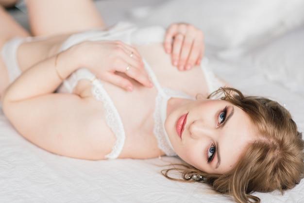 Bella giovane sposa in una biancheria bianca. ultimi preparativi per il matrimonio. la ragazza sta aspettando lo sposo.