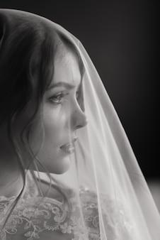 Bella giovane sposa in biancheria bianca. ultimi preparativi per il matrimonio in attesa dello sposo.
