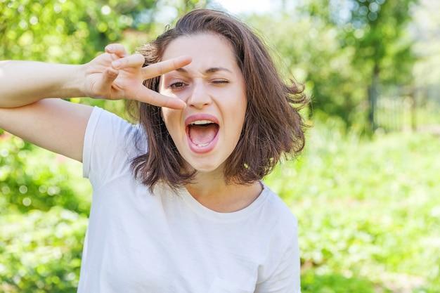 Bella giovane donna brunete che mostra la pace, la vittoria o due firmano in un parco